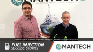 Photo of two men in front of MANTECH's backdrop. One person is holding the PeCOD Analyzer unit for water analysis.