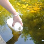plastic container collecting a sample of water from a river to be analyzed for turbidity