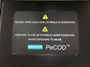 The lid / cover of the PeCOD COD Analyzer has a warning label stating 'Do not open analyzer lid while in operation. Caution, Class 3B invisible laser radiation. Avoid Exposure to beam. Mantech COD Analysis. UV LED light laser. harmful / non-harmful.