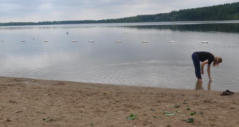 girl grabbing sample from lake